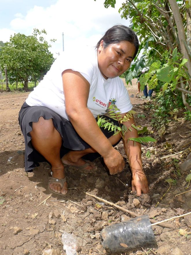 A woman plants trees near El Porvenir, El Salvador as part of a community tree planting day that brought all ages out.