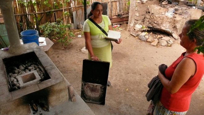Hilda visits with a clean coostove user in El Salvador.