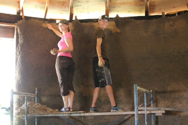 Volunteers get their hands dirty building a straw bale home.